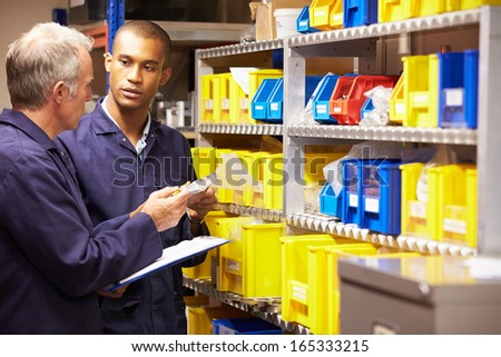 Worker And Apprentice Checking Stock Levels In Store Room - stock photo