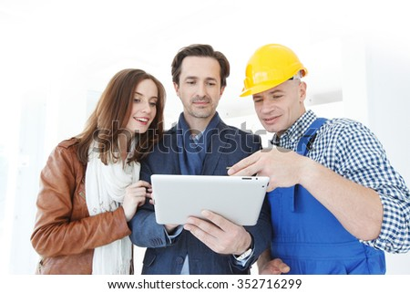 Worker and couple using tablet pc at construction site