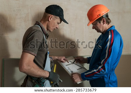 Worker and foreman discuss the scheme plasterboard ceiling in the drawing