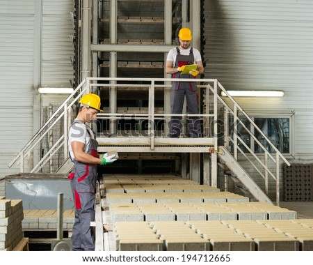 Worker and foreman in a safety hats on a factory   - stock photo