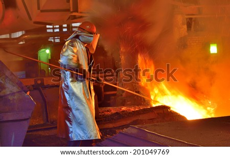 worker and production of cast iron inside of steel plant - stock photo