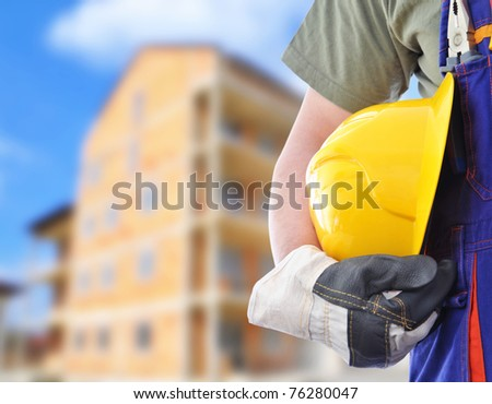 Worker and the blurred construction in background - stock photo