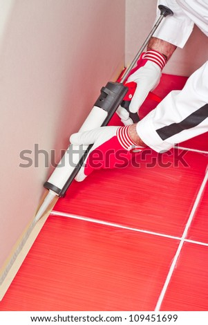 worker applies silicone sealant with gun on corner wall tiles - stock photo