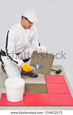 Worker Applies with Trowel Tile Adhesive on a Floor Red Tile - stock photo