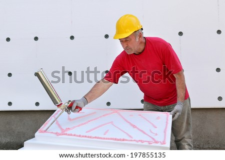 Worker applying polyurethane expanding foam glue with gun applicator - stock photo