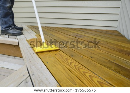 Worker Applying Stain to Deck - stock photo