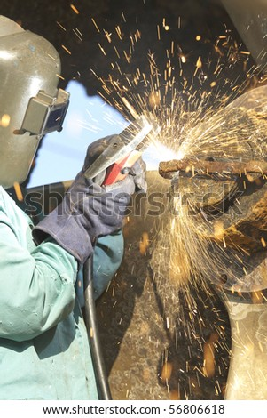 worker arcing a strap off of a tug boat wheel - stock photo