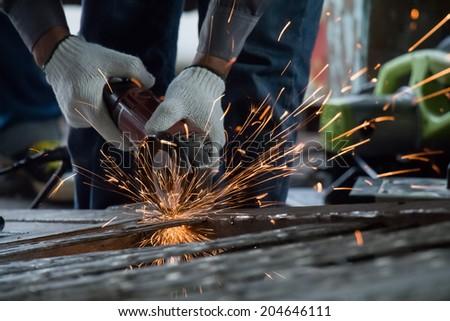 Worker are cutting steel for repair old door - stock photo