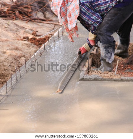 Worker are pouring the concrete with shovels at road construction  - stock photo