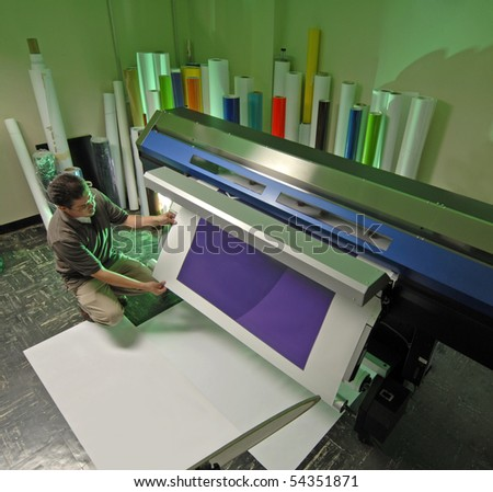 Worker at a large Inkjet printer - stock photo