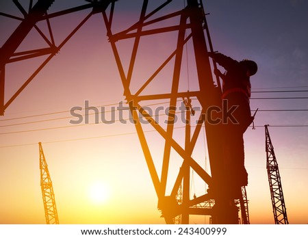 Worker at an electric substation with sunset background - stock photo