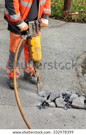 Worker at construction site demolishing asphalt with pneumatic plugger hammer