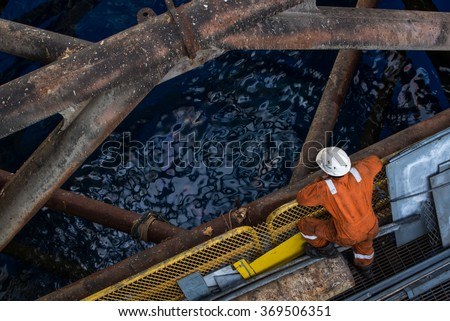 Worker at jack up oil rig leg when checking everything in rig move operation - stock photo
