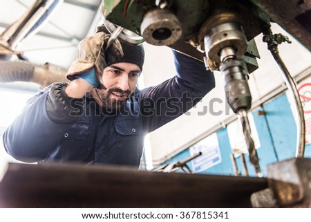 Worker at milling machine in workshop. - stock photo