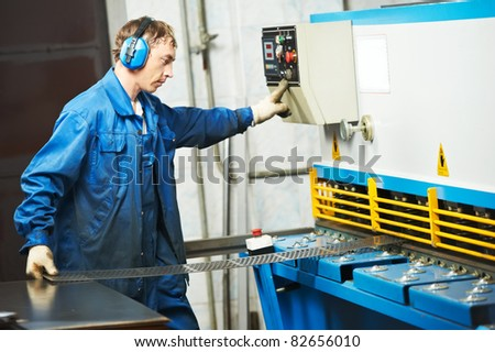 worker at workshop operating guillotine shears machine