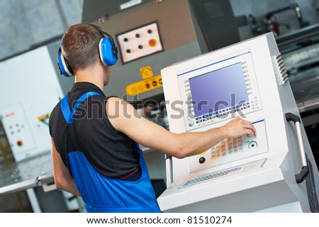 worker at workshop operating punch press machine tool by computer - stock photo