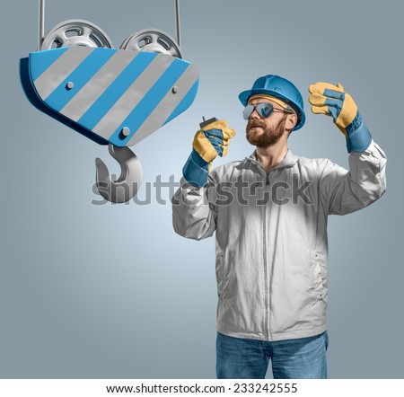 worker builder in helmet manages the construction process, crane hook on the isolated background - stock photo
