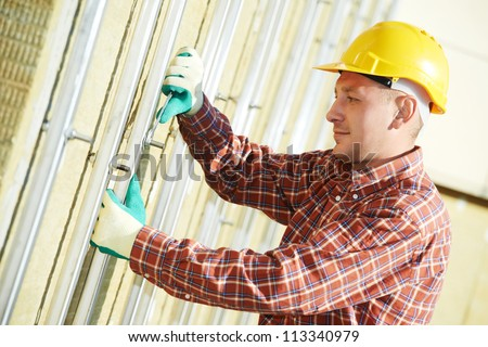 worker builder installing ventilated facade metal construction of building for granite tile - stock photo