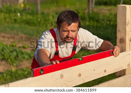 Worker building wooden fence - checking with spirit level