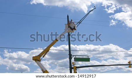 worker changing light fixture on a post - stock photo