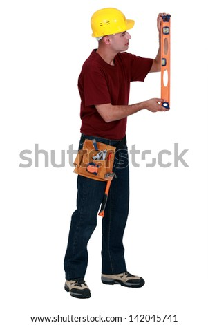Worker checking a spirit level - stock photo