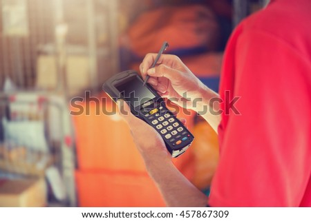 Worker Checking and Scanning Package by tablet handheld In Warehouse. - stock photo