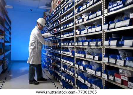 Worker checking inventory in stock room of a manufacturing company - stock photo