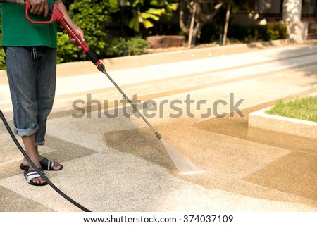 Worker cleaning outdoor floor with high pressure water jet - stock photo