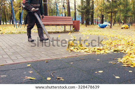 Worker cleaning playground in the autumn park from dead leaves with a blower - stock photo