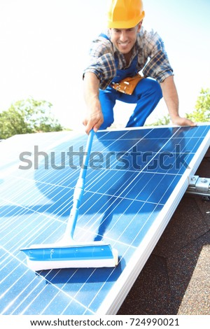 Worker cleaning solar panels after installation outdoors