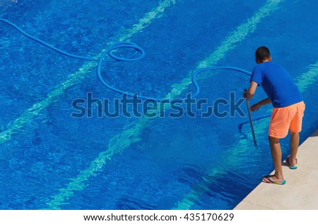 Worker cleaning the swimming pool in summer - stock photo