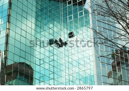worker climbing at mirror wall of office building