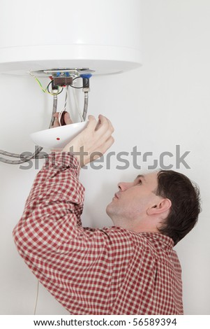 Worker connecting a water heater to the electric network - stock photo