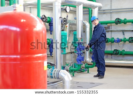 Worker controls devices in power and heating plant - stock photo