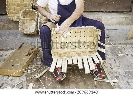 Worker craftsman making wicker chairs, work - stock photo