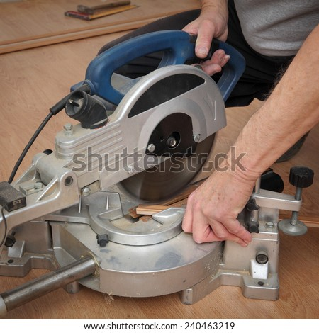 Worker cut wooden batten for laminate floor,  floating wood tile - stock photo