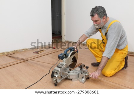 Worker cut wooden batten for laminate floor,  floating wood tile - stock photo