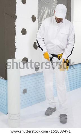 Worker cutting a fiber mesh - stock photo