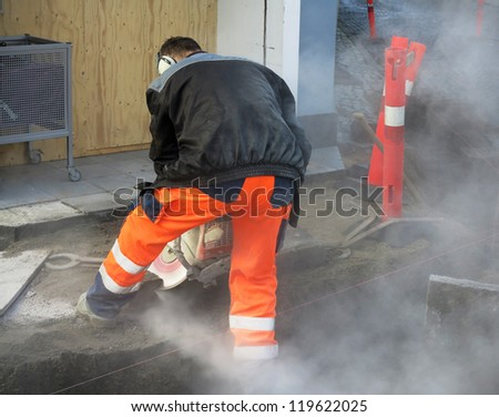 Worker cutting a granite stone in shape for kerb while constructing a new urban sidewalk somwhere in Denmark. - stock photo