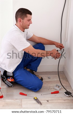 Worker cutting a wire - stock photo