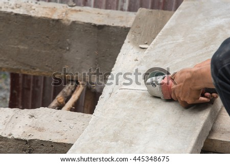 Worker cutting concrete slabs on the floor - stock photo