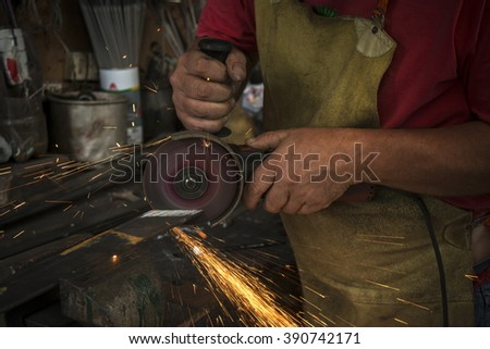 worker cutting iron plate with grinder in old metal workshop