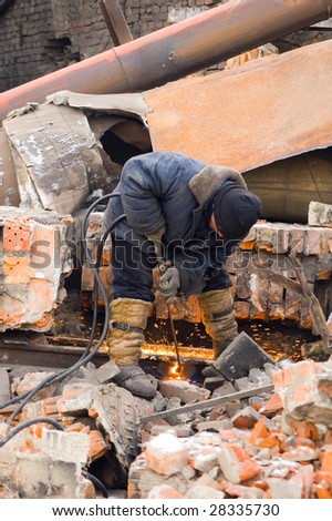 Worker cutting metal elements on old destroying factory - stock photo
