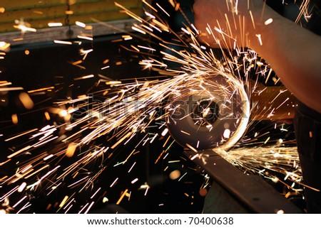 Worker cutting metal using angular grinding machine - stock photo