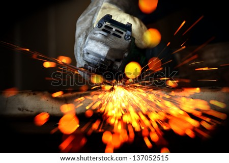 Worker cutting metal with a metal grinding sparks and bokeh - stock photo