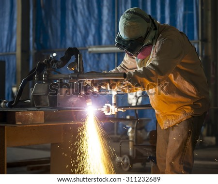 Worker cutting metal with acetylene torch close-up on low ligth - stock photo