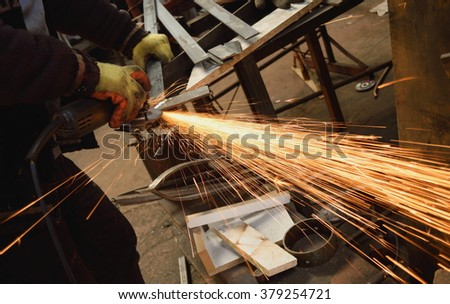 Worker cutting metal with blade in factory