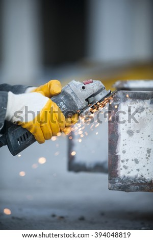 Worker cutting metal with grinder at construction site.Sparks while grinding iron - stock photo