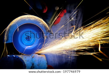 Worker cutting metal with grinder. Sparks while grinding iron - stock photo