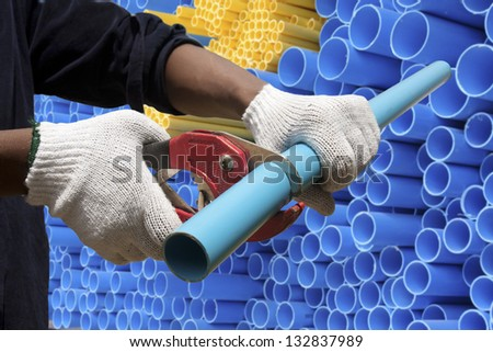 Worker cutting pvc pipe in construction site - stock photo